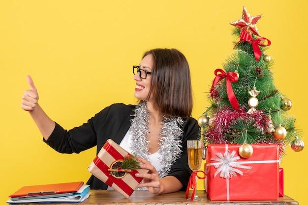 Bella dama de negocios en traje con gafas haciendo gesto ok sentado en una mesa con un árbol de navidad en la oficina