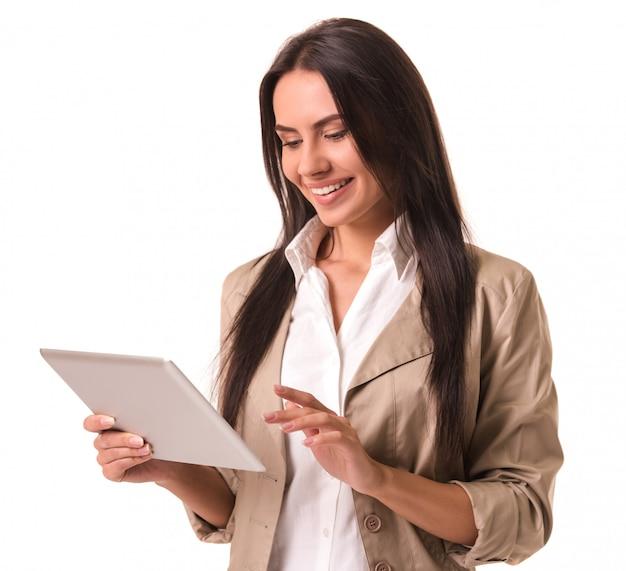 Bella dama de negocios en traje está utilizando una tableta digital.