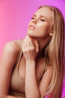 Bella dama de pie y posando sobre pared rosa