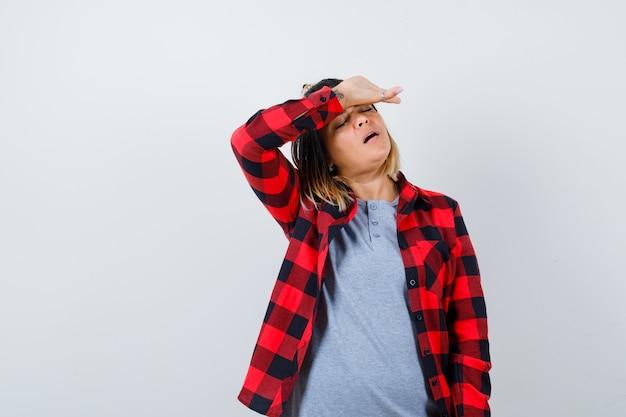 Bella dama que sufre de dolor de cabeza en ropa casual y con aspecto cansado, vista frontal.