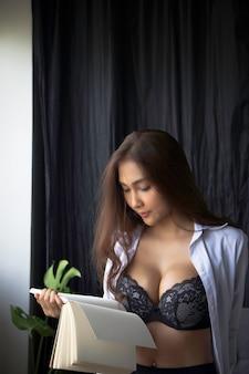 Bella dama con sostén pequeño y pantalón pequeño, libro de lectura, modelo de retrato posando, mujer sexy