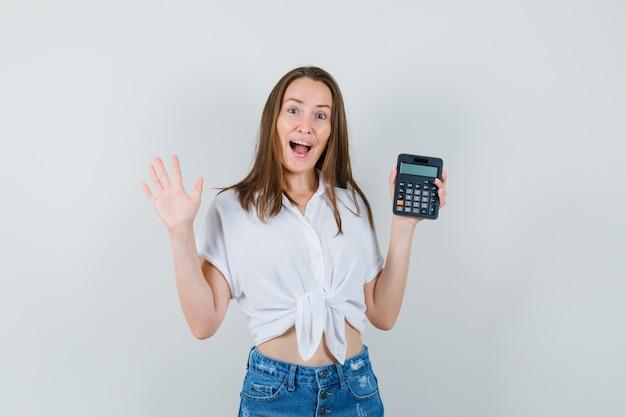 Bella dama sosteniendo la calculadora mientras agita la mano en blusa blanca, jeans y mirando enérgico, vista frontal.