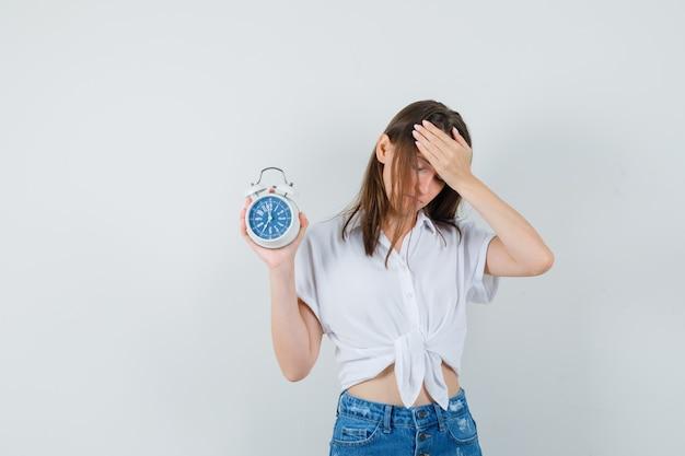 Bella dama sosteniendo el reloj mientras sostiene la mano en la cabeza con una blusa blanca y parece aburrida, vista frontal.