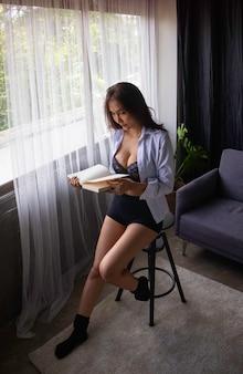 Bella dama con sujetador pequeño y pantalón pequeño, libro de lectura junto a la ventana, modelo de retrato posando, mujer sexy