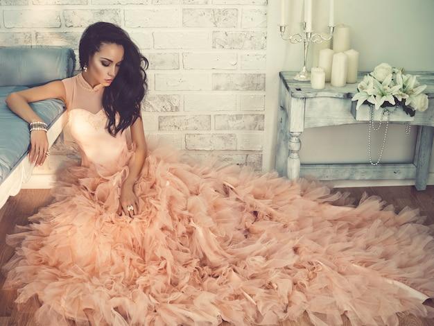 Bella dama en vestido de alta costura hermosa sentada en el suelo