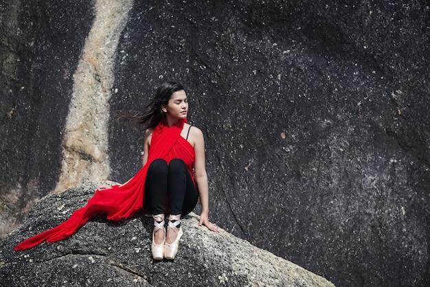 La bella dama con vestido rojo y zapatos de ballet satinado.