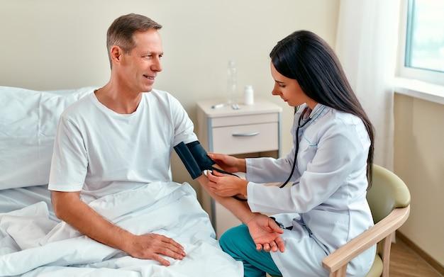 Una bella doctora mide la presión de un paciente hombre maduro que se encuentra en rehabilitación en un moderno hospital.