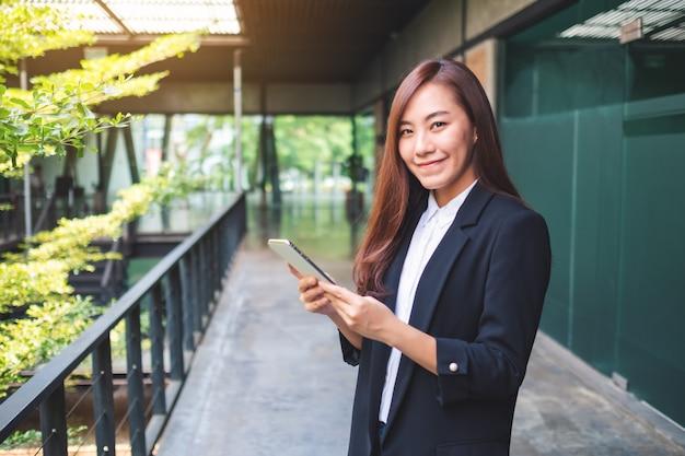 Una bella empresaria asiática sosteniendo y usando el teléfono móvil en la oficina