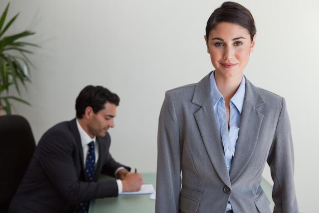 Bella empresaria posando mientras su colega está trabajando