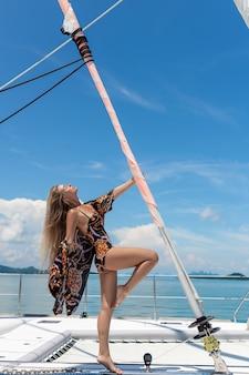 Una bella y encantadora rubia con el pelo largo en un traje de baño de color con un abrigo de playa, posando con una mano sujetando un poste con una vela retorcida. yate. vacaciones ricas.