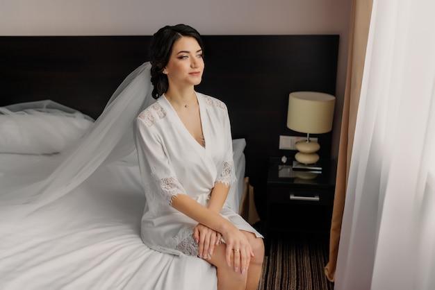 Una bella y feliz novia morena con bata blanca está sentada en la cama y mirando por la ventana. retrato de boda de una niña alegre. novia en la mañana de la boda