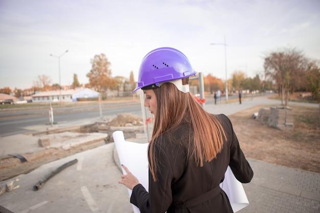 La bella inspectora en las manos sostiene el proyecto y revisa las obras subterráneas.