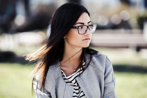 Bella modelo en gafas sentarse en la valla