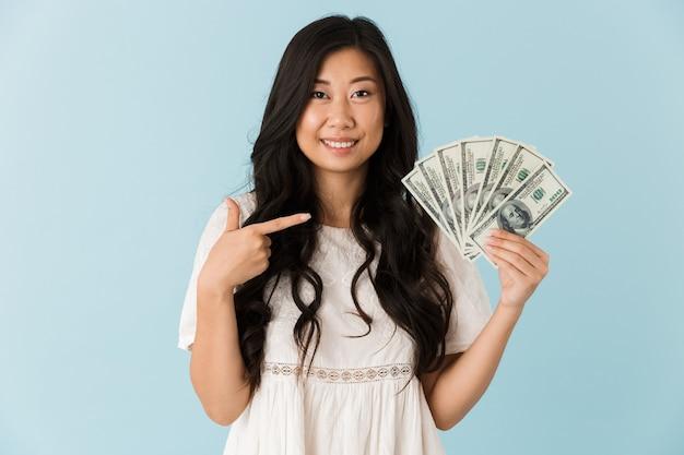 Bella mujer aislada sobre pared azul sosteniendo dinero