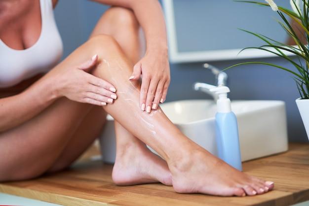 Bella mujer aplicando bálsamo en las piernas en el baño.