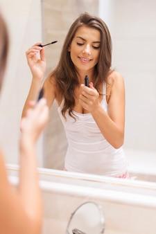 Bella mujer aplicando rímel en el baño.