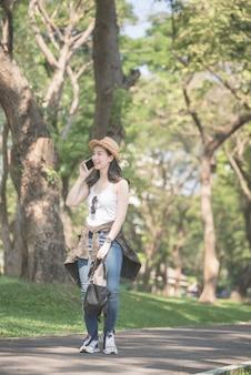 La bella mujer asiática solitaria que sonríe y disfruta tomando por teléfono móvil