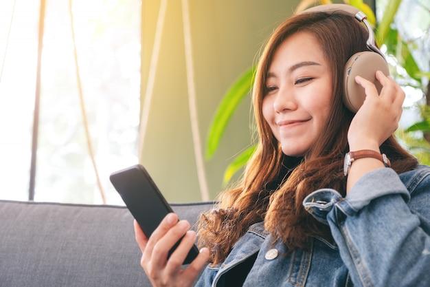 Una bella mujer asiática utilizando teléfono móvil y auriculares para escuchar música