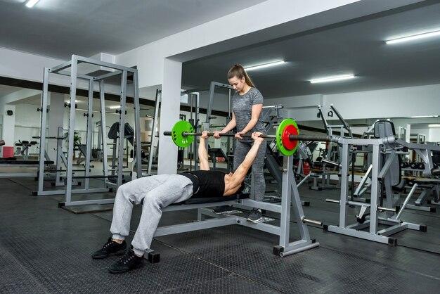Bella mujer ayudando a los hombres a levantar pesas