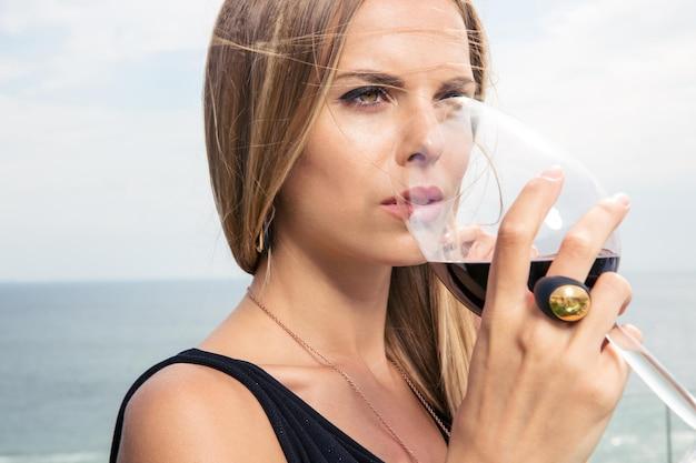 Bella mujer bebiendo vino en la cafetería al aire libre