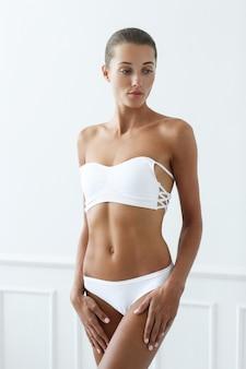 Bella mujer en bikini blanco
