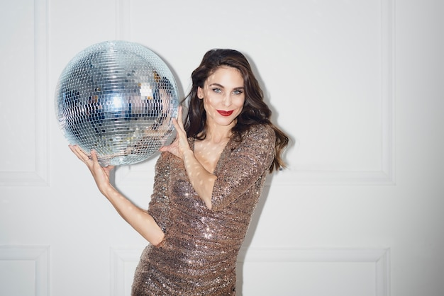 Bella mujer con bola de discoteca