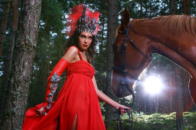 Bella mujer con caballo marrón