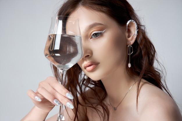 Bella mujer con cabello castaño con vaso