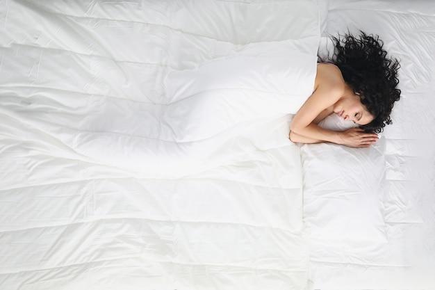 Bella mujer con cabello rizado duerme dulcemente en la cama cubierta con una manta.