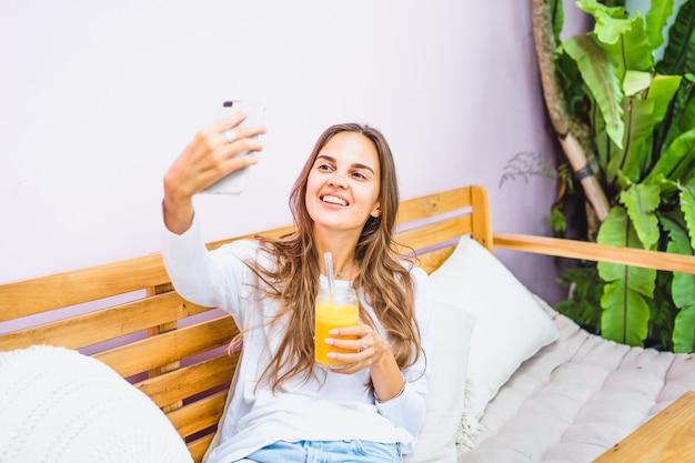 Una bella mujer en un café hace selfie en un teléfono inteligente, bebe zumo recién exprimido.