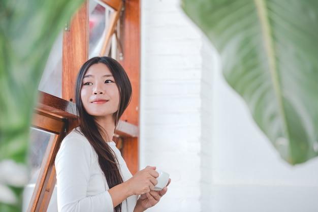 Una bella mujer con una camisa blanca de manga larga sentada en una cafetería.