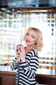 Bella mujer canta con un micrófono