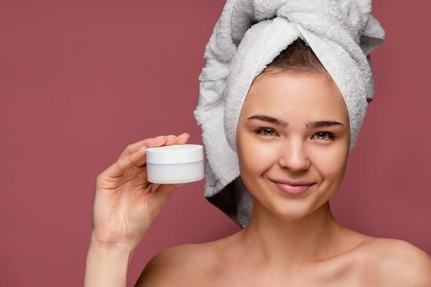 Bella mujer con crema facial