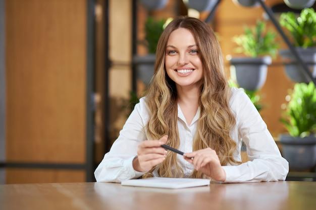 Bella mujer dando entrevista o comunicándose en el café