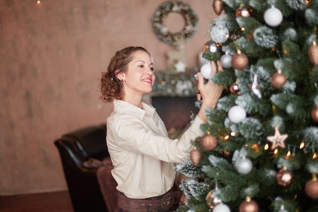 Bella mujer decorar el árbol de navidad en su sala de estar