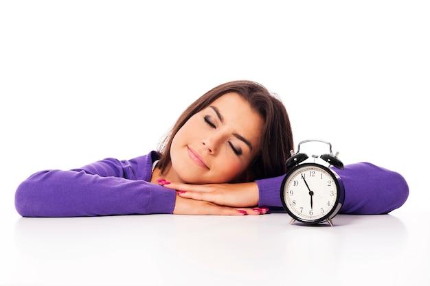 Bella mujer durmiendo con despertador