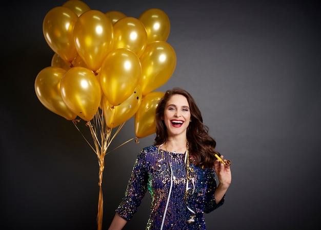 Bella mujer con globos dorados en tiro de estudio