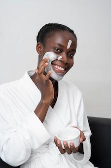 Bella mujer haciendo un tratamiento facial en casa