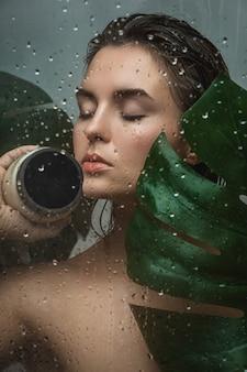 Bella mujer con una hoja tropical capturada a través de vidrio mojado