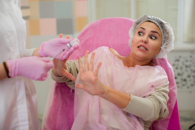 Una bella mujer horrorizada se protege las manos de la jeringa para inyección.