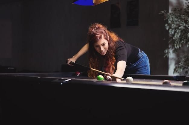 Bella mujer jugando al billar