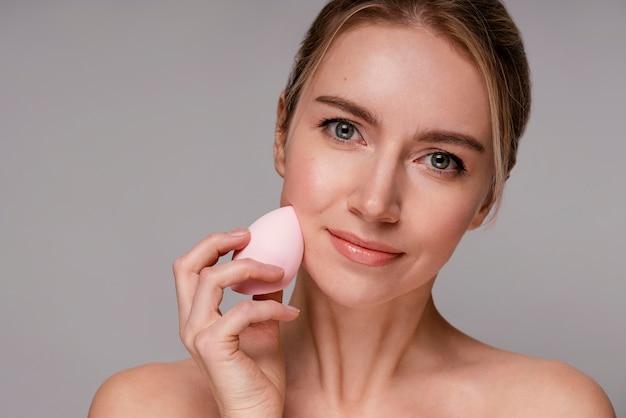 Bella mujer con una licuadora de maquillaje
