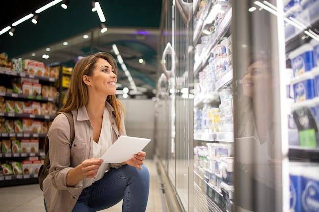 Bella mujer con lista de compras comprando alimentos en el supermercado