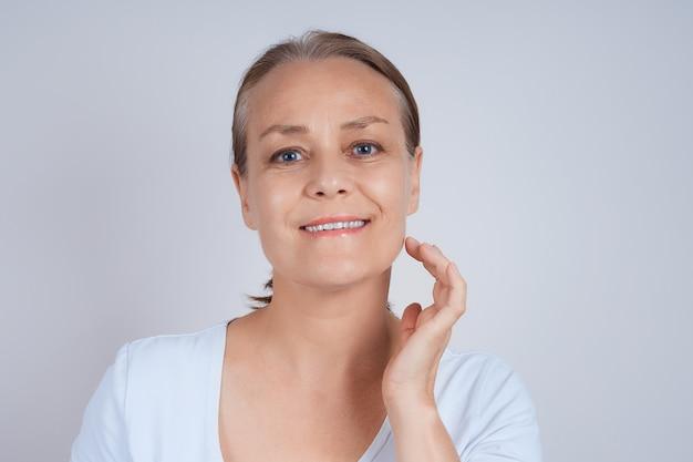 Una bella mujer madura disfruta de su perfecta piel facial, se lleva los dedos a la mejilla.