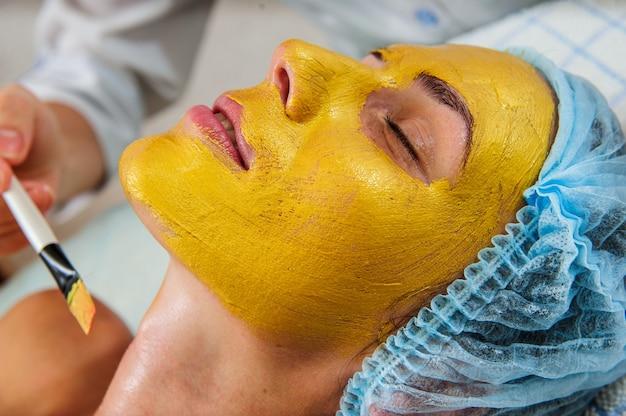 Bella mujer con máscara de oro facial en el salón de belleza