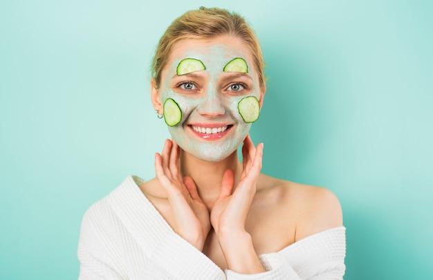 Bella mujer con mascarilla facial para el cuidado de la piel y rodajas de pepino procedimiento cosmético tratamientos de belleza