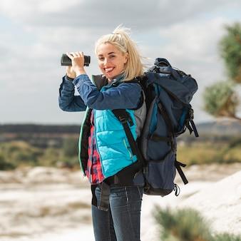 Bella mujer con mochila y binoculares