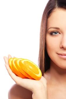Bella mujer con naranja en manos