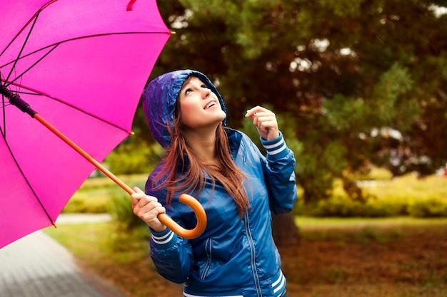 Bella mujer con paraguas mirando al cielo