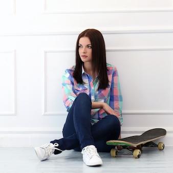 Bella mujer con patineta